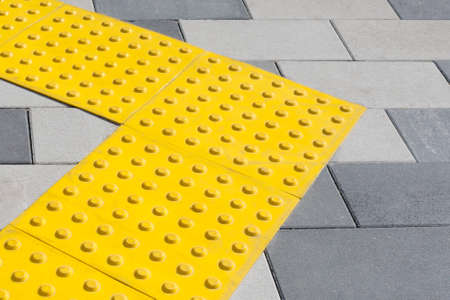 Yellow blocks of tactile paving for blind handicap. Braille blocks, tactile tiles for the visually impaired, Tenji blocks. Textured ground surface indicators located on sidewalks, stairs