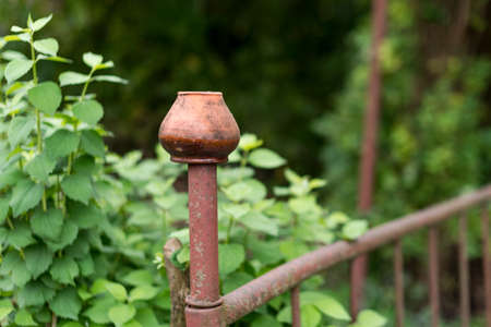 Clay jug hanging on the fence in the garden. Traditional ukrainian pottery. Brown pottery used as garden decor.