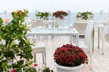 Blurred background, empty tables and chairs of a restaurant on a terrace overlooking the sea. Cafe with sea view. Nice place to eat with seaview. Selective focus