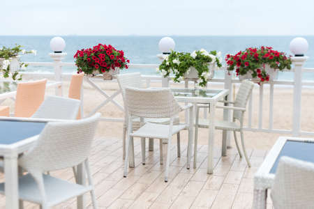 Empty tables and chairs of a restaurant on a terrace overlooking the sea. Cafe with sea view. Nice place to eat with seaview. Selective focus Archivio Fotografico