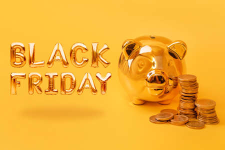 Golden piggy bank with money towers on yellow background with text Black Friday. Stack of euro coins near golden money box. Money pig, money saving, moneybox, sale and discount concept Archivio Fotografico