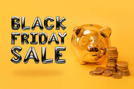 Golden piggy bank with money towers on yellow background with text Black Friday Sale. Stack of euro coins near golden money box. Money pig, money saving, moneybox, sale and discount concept