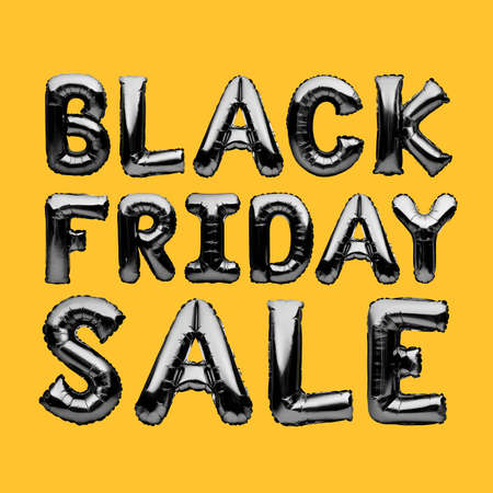 Black helium balloons forming the words BLACK FRIDAY SALE isolated on yellow background. Chrome black inflatable balloons, sale, discount, black friday concept Archivio Fotografico