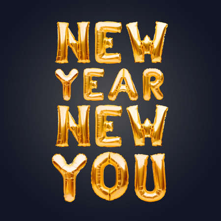 New Year New You phrase made of golden inflatable balloons on dark background. Helium balloons, foil celebration decoration. New start, self improvement, business, career change, new goal concept