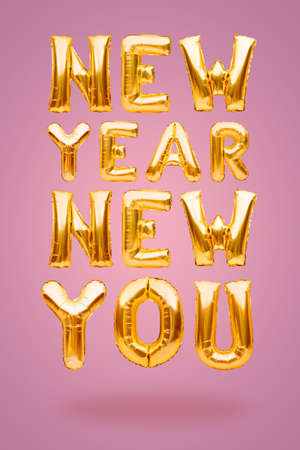 New Year New You phrase made of golden inflatable balloons on pink background. Helium balloons, foil celebration decoration. New start, self improvement, business, career change, new goal concept