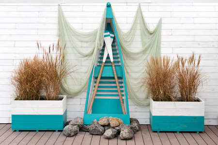 Nautical concept with decorative fishing net, wooden boat and paddles. Outdoor location in marine style for a photo shoot
