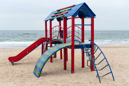 A children's play area for active games on a beach. Colorful empty playground in a park near the sea. Improvement of public spaces. Standard-Bild