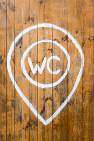 WC sign with white painted text on wooden wall. 版權商用圖片