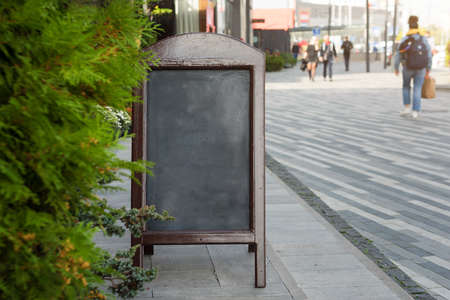 Signboard on the street. Empty menu board stand. Restaurant sidewalk chalkboard sign board. Freestanding A-frame blackboard near outdoor cafe. Copyspace for text, selective focus.