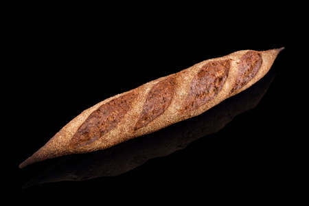 Freshly baked homemade bread isolated on black. French bread baguette. Healthy eating and traditional bakery, baking bread concept.