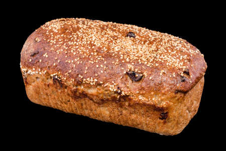 Freshly baked homemade bread isolated on black. Rye bread with red berries and sesame. Healthy eating and traditional bakery, baking bread concept.