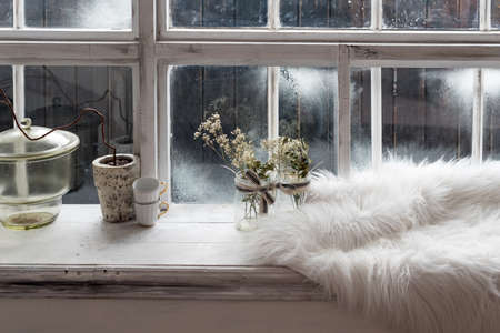 Cozy winter still life. Dried plants, small coffee cups and warm fur on vintage kitchen windowsill. Winter season, spending winter time at cozy home concept.