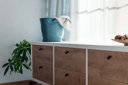 Laundry basket with gray towel. Interior of white stylish room with laundry basket.