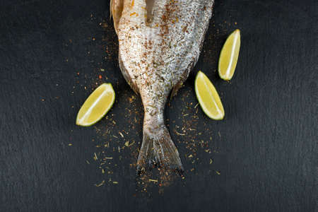 Tail of fresh raw dorado on black slate stone board with spices, herbs and lime. Sea bream fish ready for cooking. Top view