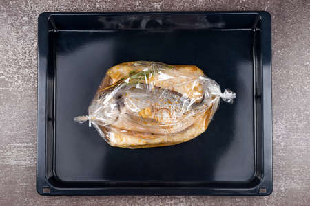 Fish in baking bag. Dorado fish with rice, sauce and herbs wrapped in a baking sleeve in oven ready for cooking. Mediterranean cuisine, european dish. Фото со стока