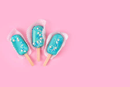 Tasty and refreshing ice cream on sticks. Blue mint ice cream  on pastel pink background. Minimal summer concept. Flat lay.
