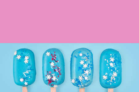 Tasty and refreshing ice cream on sticks. Blue mint ice cream  on blue and pink background. Minimal summer concept. Flat lay, free copyspace for text