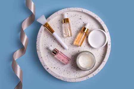 Hydrating anti aging serum with collagen and peptides in glass bottle with dropper. Skin care essence glass bottles and jar with facial cream on marble cosmetic tray on blue background.