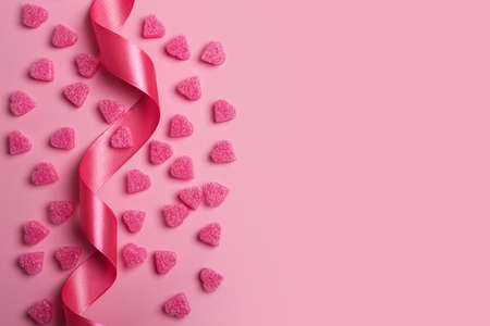 Pink hearts on pastel pink background with ribbon. Romantic background for Valentine's Day. Valentine day concept, design for banner or gift card. Flat lay, top view, copy space. Фото со стока