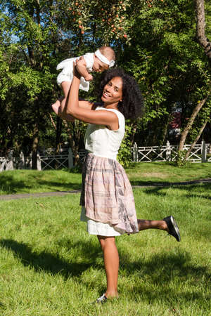 Young african american woman and her daughter smiling walking in summer park. Mother playing with her baby girl outdoors. Cute baby on moms hands outside. Family in the park in summer.