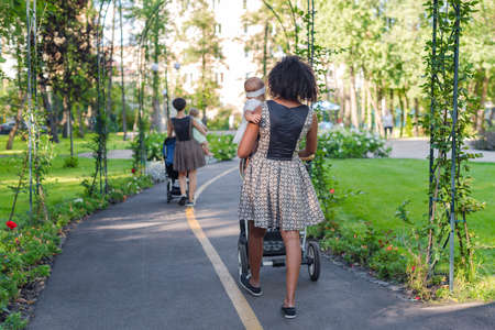 Two young mothers pushing strollers in summer park. Women in the park walking with strollers Imagens