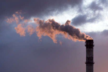 Industrial smoke from chimney on dramatic sundown sky. Factory pipe sending smoke to the atmosphere, air pollution of industry