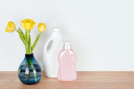 Bottles of detergent and fabric softener with yellow tulip flowers on wooden table. Containers of cleaning products. Liquid detergent and conditioner. Laundry day, cleaning concept. Copyspace for text