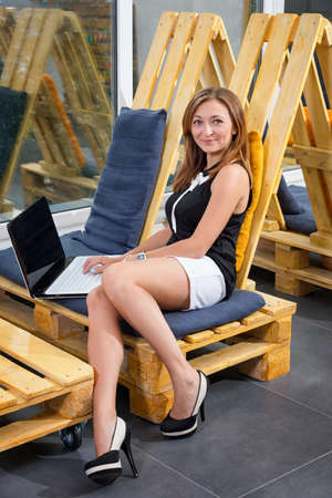 Young businesswoman working with new startup project using laptop computer in modern loft. Casually dressed female freelancer at coworking space.
