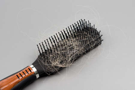Hair loss problem, hairbrush with a lot of fallen hairs on gray background. Bunch of blonde hair on the comb. Losing too much hair. Healthcare concept