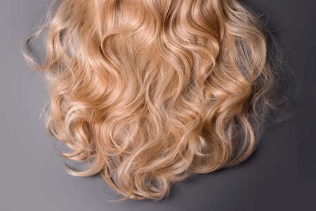 Blonde hair texture. Wavy long curly blond hair close up as background. Hair extensions, materials and cosmetics, wig, hair care. Hairstyle, haircut or dying in salon
