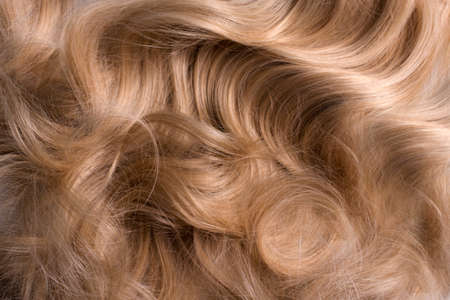 Blonde hair texture. Wavy long curly blond hair close up as background. Hair extensions, materials and cosmetics, hair care. Hairstyle, haircut or dying in salon