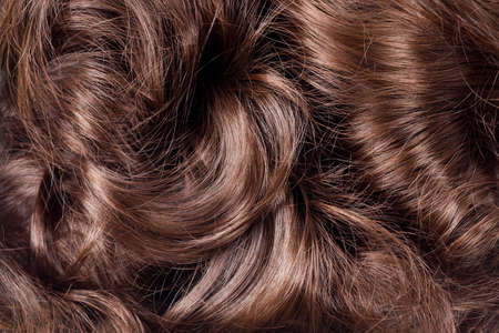 Brown hair texture. Wavy long curly light brown hair close up as background. Hair extensions, materials and cosmetics, hair care. Hairstyle, haircut or dying in salon.