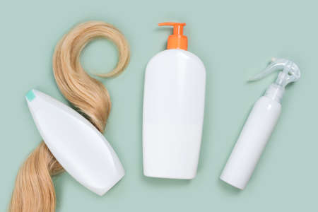 Shampoo wrapped in lock of curly blonde hair, conditioner bottle and hair spray mockups on mint background, top view. Flat lay in pastel colors. Hair care cosmetics, haircare products, hair treatment