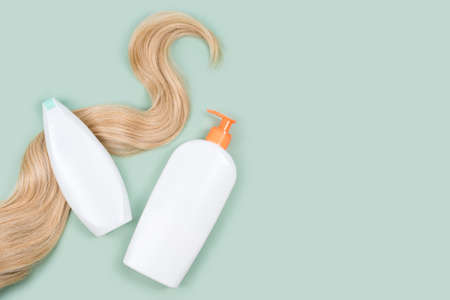 Shampoo wrapped in lock of curly blonde hair and conditioner bottle mockups on mint background, top view. Flat lay in pastel colors. Hair care cosmetics, haircare products, hair treatment