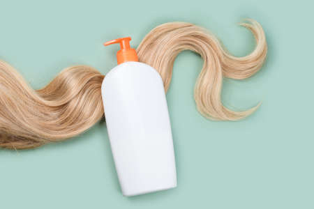 Shampoo or conditioner bottle wrapped in lock of curly blonde hair on light mint background, top view.Flat lay in pastel colors, mockup. Hair care cosmetics, beauty haircare products, hair treatment Imagens