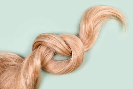 Blonde hair lock tied in knot. Strand of honey blonde hair on mint background, top view. Hairdresser service, hair strength, haircut, hairstyle, dying or coloring, hair extension, treatment concept.
