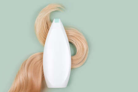 Shampoo or conditioner bottle wrapped in lock of curly blonde hair on light mint background, top view. Flat lay in pastel colors, mockup. Hair care cosmetics, beauty haircare products, hair treatment Imagens