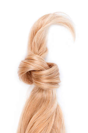 Blonde hair lock tied in knot. Strand of honey blonde hair isolated on white background, top view. Hairdresser service, hair strength, haircut, dying or coloring, hair extension, treatment concept