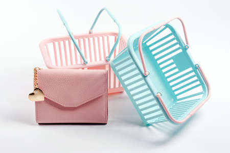 Colorful plastic shopping baskets with leather wallet. Empty pink and blue supermarket baskets on light gray background. Creative design, shopping, black friday, discount, advertising, sale concept