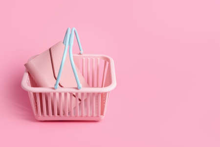 Colorful plastic shopping basket with leather wallet. Empty pink and blue supermarket basket on pink pastel background. Creative design, shopping, black friday, discount, advertising, sale concept