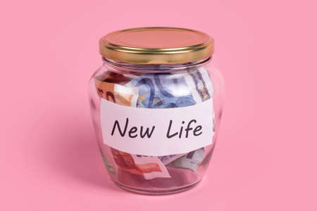 Money box with words New Life on sticky note paper. Euro banknotes in glass money jar with savings label, financial, saving. Jar full of cash, save money concept, expense control
