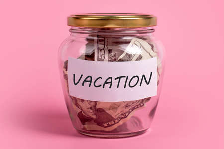Vacation budget concept. Money box with word VACATION on sticky note paper. Dollars in glass money jar with savings label, financial, saving. Jar full of american dollar bills, cash, planning, travel.