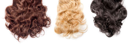 Brown, blonde and black hair on white background. Wavy long different curly hair. Hair extensions, materials and cosmetics, hair care, wig. Hairstyle, haircut or dying in salon, banner.