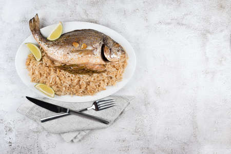 Fresh grilled dorado or sea bream fish with lemon and rosemary served with rice. Delicous dorada fish cooked on grill in seafood restaurant. Healthy food. Top view, free copy space.
