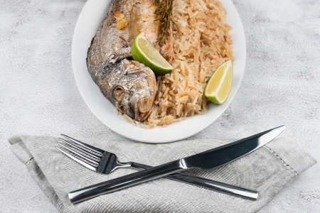Fresh grilled dorado or sea bream fish with lemon and rosemary served with rice. Delicous dorada fish cooked on grill in seafood restaurant. Healthy food