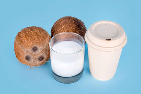 Coconuts with a glass of coconut milk and paper coffee cup on blue background. Healthy vegan food, lactose free diet, milk alternative, coffee to go, vegan latte or coconut cappuccino. Imagens