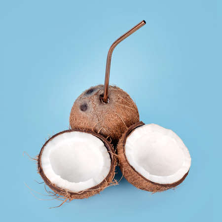 Open coconut with straw on blue background. Tropical drink, summer vacation minimal creative concept. Cracked coconut fruit with coconut milk inside. Imagens