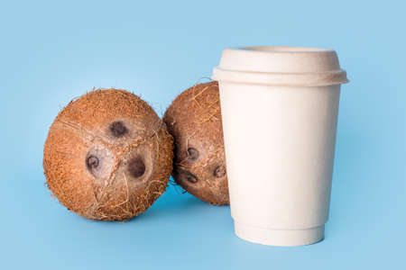 Coconuts with paper coffee cup on blue background. Healthy vegan food, lactose free diet, milk alternative, coffee to go, vegan latte or coconut cappuccino.