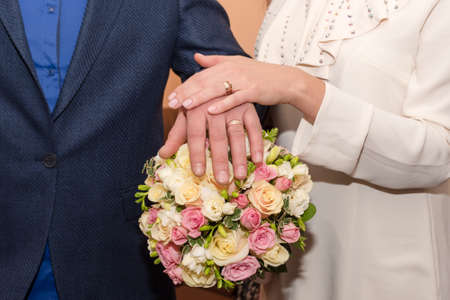 Bride and groom holding hands showing their rings, wedding couple holding bouquet Imagens