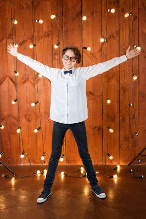 Smart teenager wearing glasses posing in loft apartment. Teenage girl in white shirt on light bulbs background